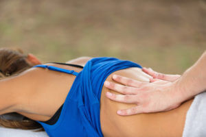 Physiotherapist giving sports massage of a lower back